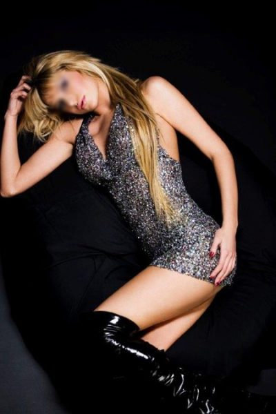 girl in sparkly dress laid on a black sofa