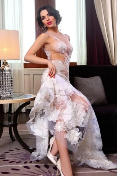 brunette poses in grand dress in her hotel room