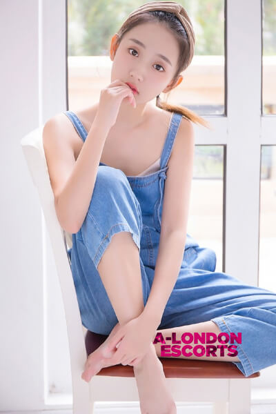 chinese girl poses in blue dungarees