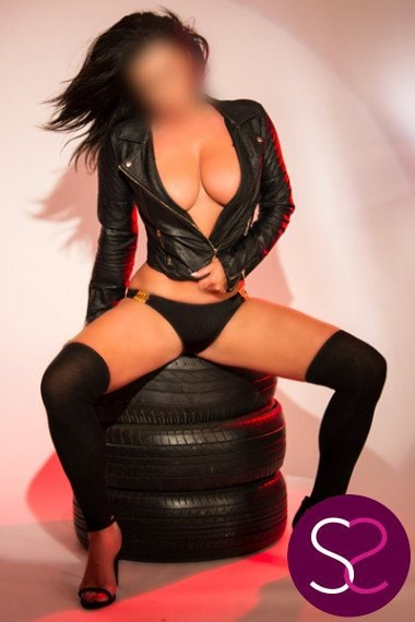 busty biker in leathers sat on tyres