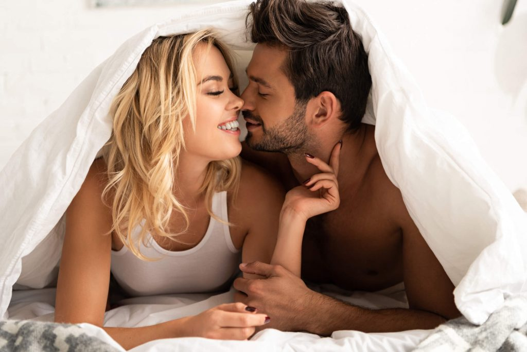 man and woman under the sheets kissing