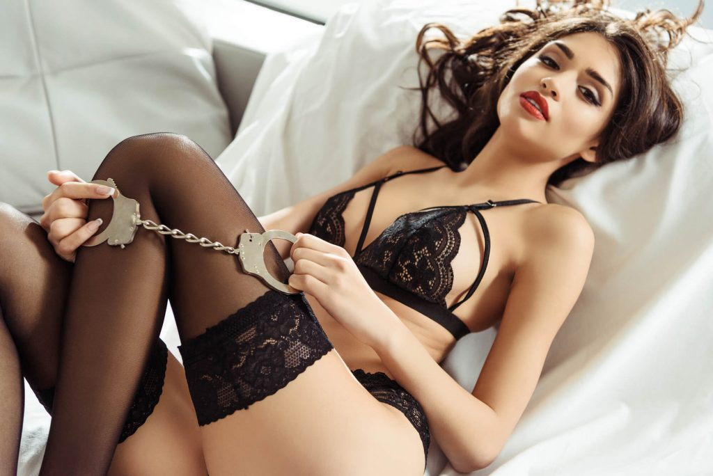 girl holding handcuffs on the bed