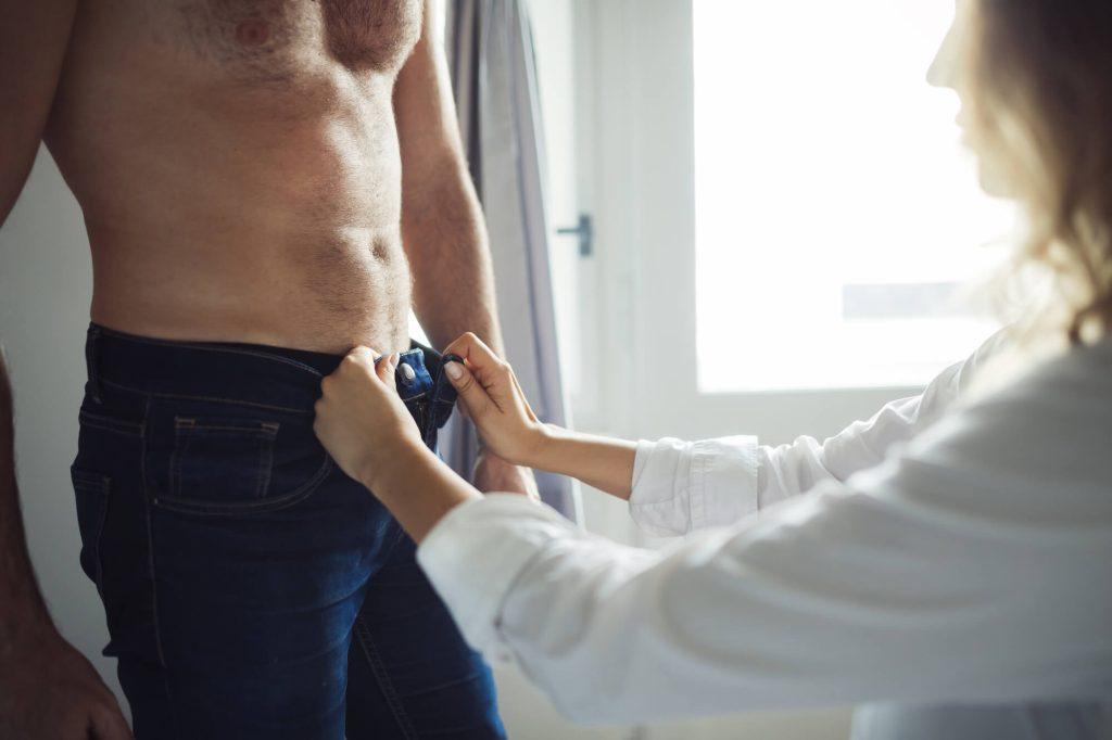 woman unbuttoning a mans jeans