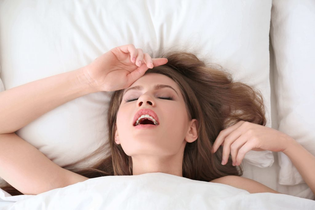 woman reaching orgasm in bed