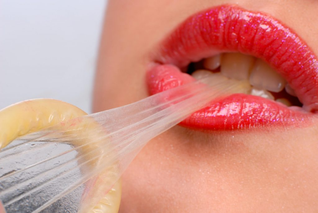 woman biting a condom