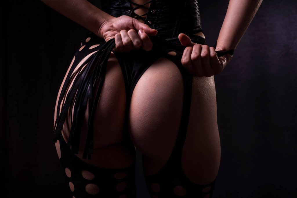 close up of ass with a woman holding a whip