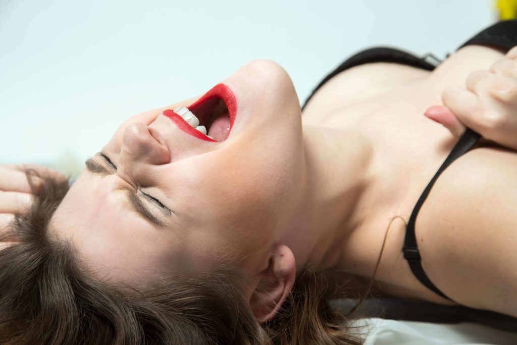 woman wearing red lipstick reaching orgasm