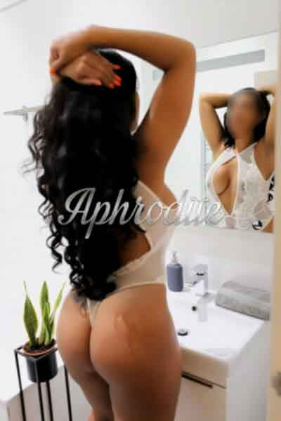 long haired black haired escort posing in the mirror