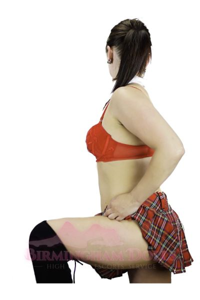 side view of an escort in a tartan skirt and black stockings