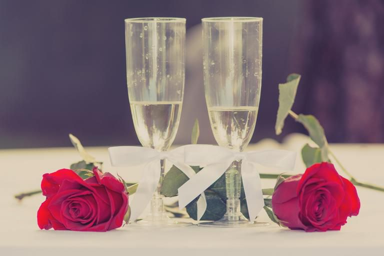 two glasses of win surronded by roses