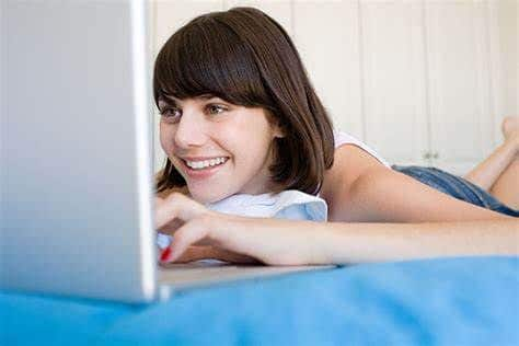 A girl on her bed using her laptop