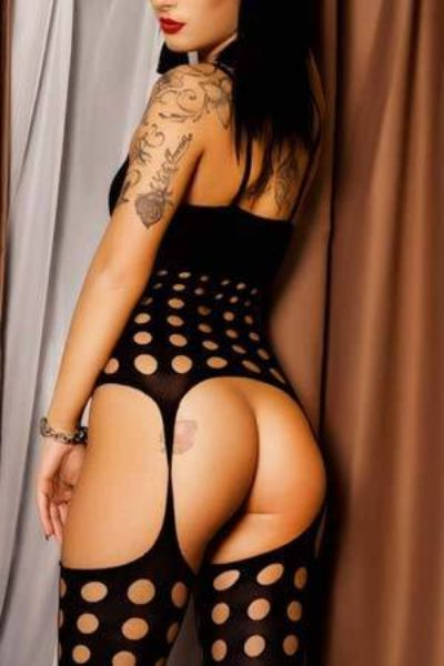 tattooed escort showing her naked ass