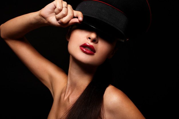 model in bright red lipstick holding cap