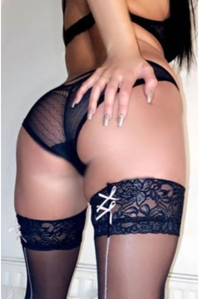 model with laced up black stockings has hand on ass