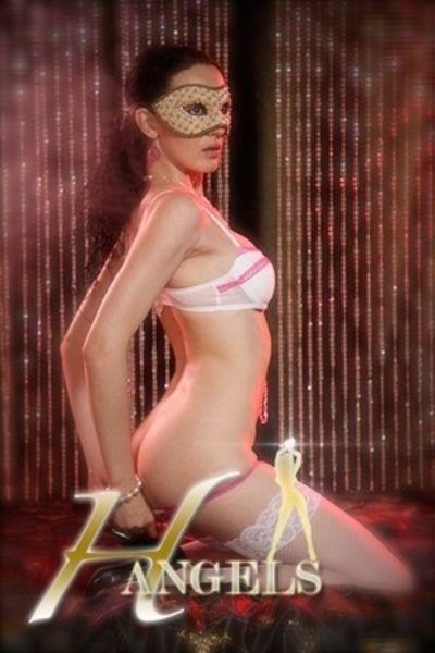 Brunette in white lingerie has hands behind her back
