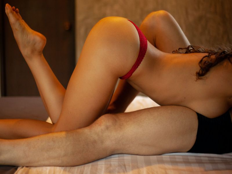 sexy woman in red panties climbing on her man