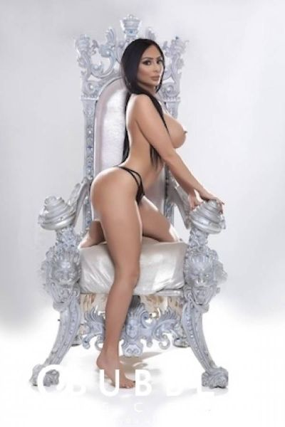 escort with huge tits poses by a grand silver chair