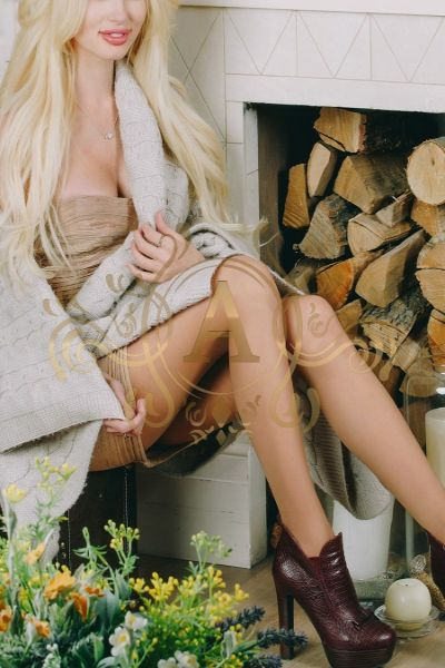 Long haired escort in leather boots sitting and smiling
