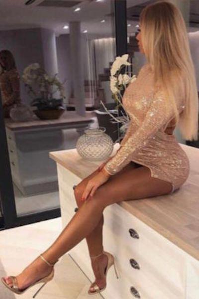 classy escort sitting on kitchen counter