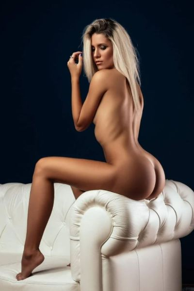 naked blonde perched on sofa arm