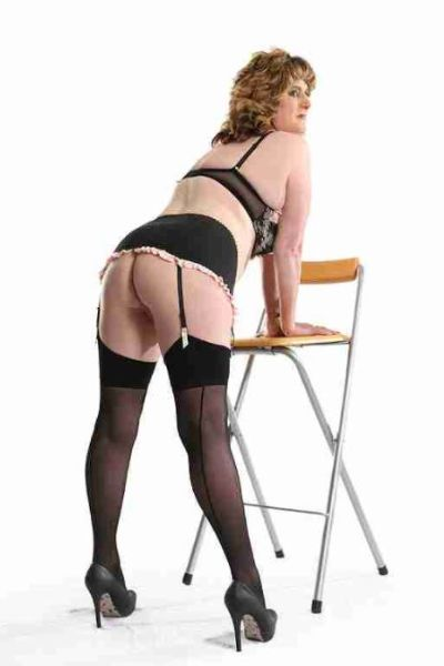 mature escort bending over a high stool