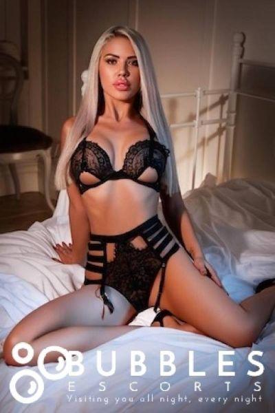 fit escort posing on bed in black lingerie