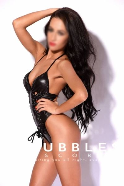 long black haired escort posing in black patent leather outfit