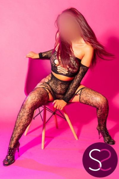 long flame haired escort sat on a chair
