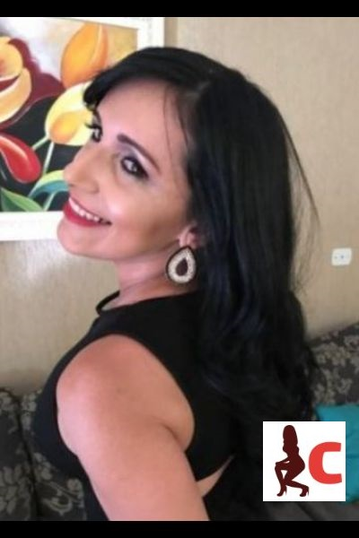 black haired escort smiling and modelling